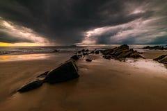 在海滩的岩石是风雨如磐的 免版税库存照片