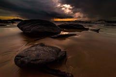 在海滩的岩石是风雨如磐的 库存图片