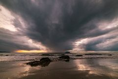 在海滩的岩石是风雨如磐的 免版税库存图片