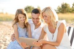 在海滩的微笑的家庭与片剂个人计算机计算机 免版税库存照片