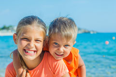 在海滩的微笑的愉快的孩子 免版税库存图片