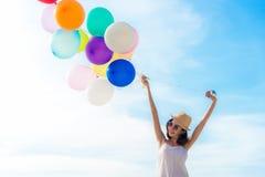 在海滩的微笑的生活方式亚洲妇女冷颤手藏品气球 在暑假放松并且享用 免版税库存照片