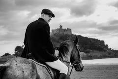 在海滩的悦目雄性马车手骑乘马在有圣迈克尔` s登上的传统骑马衣物在背景中 免版税库存照片