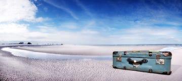 在海滩的手提箱 库存图片