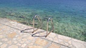 在海滩的扶手栏杆游泳海 钢扶手栏杆,游泳,蓝色海,海边,波浪,夏天,旅行,自然环境 股票录像