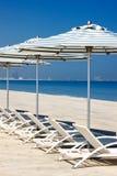 在海滩的斜倚的轻便折叠躺椅 免版税库存图片