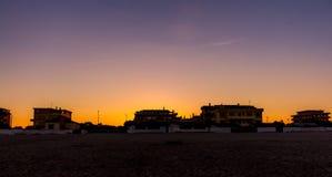 在海滩的日出颜色在城市 库存照片