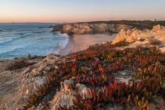 在海滩的日落与岩石在波尔图Covo在阿连特茹,葡萄牙 图库摄影