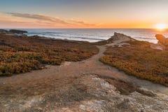 在海滩的日落与岩石在波尔图Covo在阿连特茹,葡萄牙 库存照片