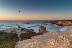 在海滩的日落与岩石在波尔图Covo在阿连特茹,葡萄牙 免版税库存图片