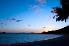 在海滩的日落与棕榈和海洋哈密尔顿岛,大堡礁,澳大利亚 免版税图库摄影
