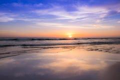 在海滩的日落与轻的金黄时间和紫罗兰色天空反射表面上 库存图片