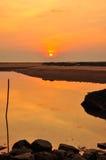 在海滩的日落和石头 免版税库存照片