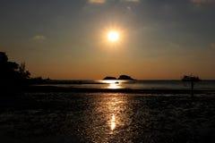 在海滩的日落时间有橙色天空背景 免版税库存图片