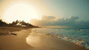 在海滩的日落是在沙子漂浮的反射波 多米尼加共和国自然日落 股票录像