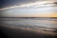 在海滩的日落用桔子填装了多云天空 免版税库存图片