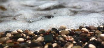 在海滩的明亮的五颜六色的石头与清楚的清楚的水,泡沫似的波浪,横幅和纹理的 焦点奔跑通过中部 库存照片