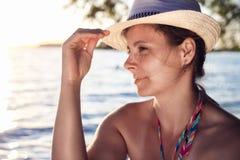 在海滩的有吸引力的被晒黑的性感的逗人喜爱的夫人佩带的帽子在日落在一个温暖的夏天晚上 海海滩的梦想的优美的妇女 库存图片