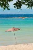 在海滩的木席子伞 免版税图库摄影