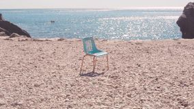 在海滩的椅子反对海 股票 老偏僻的椅子在石海滩站立反对蓝色美丽的海和清楚的天空 股票录像