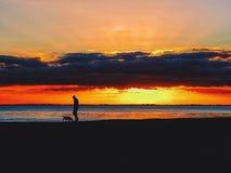 在海滩的步行在日落 免版税图库摄影