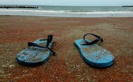 在海滩的残破的凉鞋 免版税库存图片