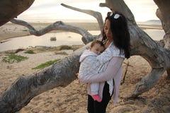 在海滩的母亲和儿童债券 免版税库存图片