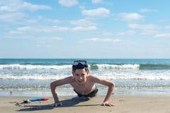 在海滩的沙子和管的男孩绞的潜航的面具在海背景 体育的概念 免版税库存照片