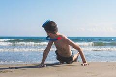 在海滩的沙子和管的男孩绞的潜航的面具在海背景 体育的概念 免版税图库摄影