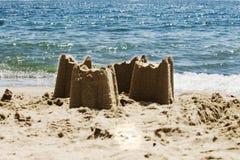 在海滩的沙子城堡与海在背景,s中 免版税库存图片