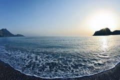 在海滩的泡沫波浪在黎明 免版税库存图片