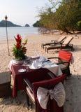 在海滩的浪漫日落正餐 免版税库存图片