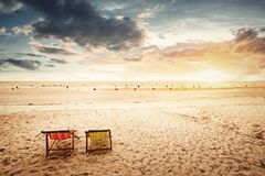 在海滩的海滩睡椅与日落 免版税图库摄影