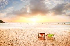 在海滩的海滩睡椅与日落 库存图片
