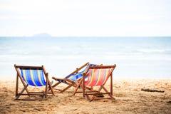在海滩的海滩睡椅与海水 免版税库存图片