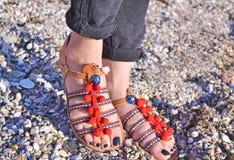 在海滩的漂泊凉鞋广告-希腊皮革凉鞋 库存照片