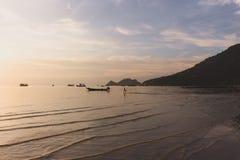 在海滩的热带日落与孩子赛跑 库存照片