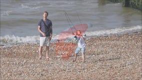 在海滩的父亲和儿子kitesurfing的训练 股票录像
