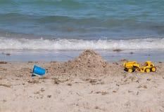 在海滩的玩具在水附近 库存图片