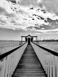 在海滩的码头反对多云天空和港口 免版税库存照片