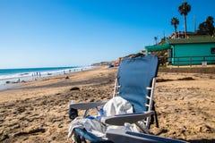 在海滩的空的蓝色海滩睡椅由海洋 库存照片