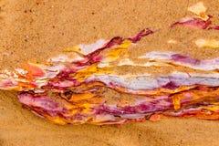 在海滩的红土岩石 免版税库存图片