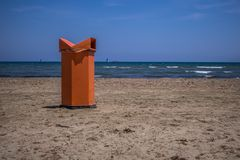 在海滩的红色垃圾桶有海背景 免版税库存图片