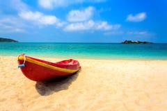 在海滩的红色小船与蓝色海和蓝天 库存照片