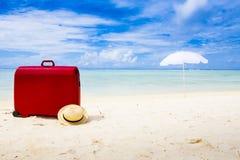 在海滩的红色手提箱 免版税库存照片