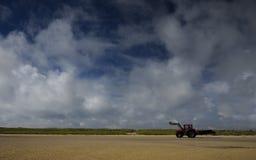 在海滩的红色拖拉机 免版税库存图片