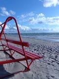 在海滩的红色长凳 免版税库存图片