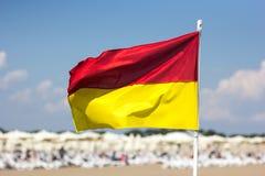 在海滩的红色黄旗 生活安全的概念  库存图片