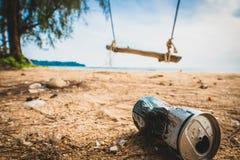 在海滩的罐头毁坏环境 在沙子的垃圾在自然 垃圾在与摇摆的一个美丽的海滩 图库摄影
