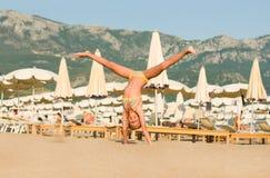 在海滩的美好的愉快的女孩翻筋斗 图库摄影